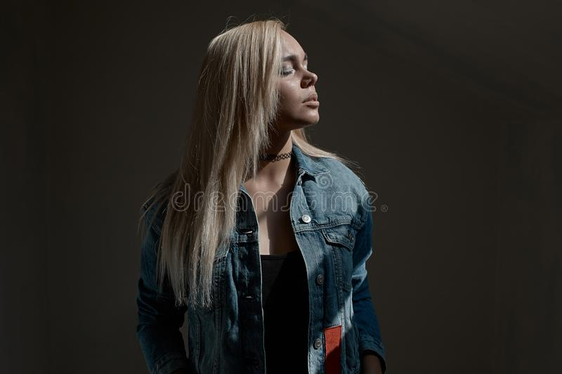 Portrait of young blond woman on dark background stock photo