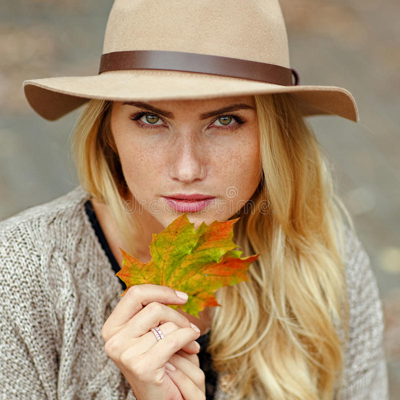 Portrait of a young blond woman with freckles wearing a hat in t stock photo