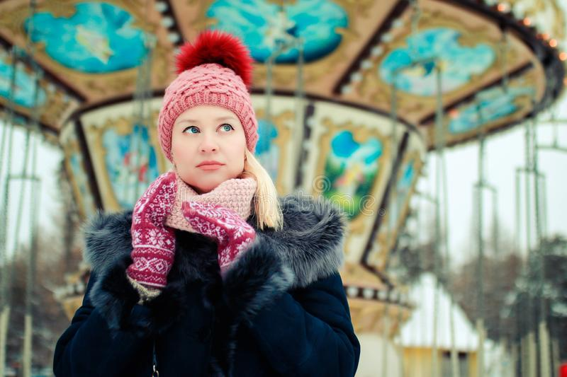 Portrait of young blond woman in winter clothes. Red cap and mittens. Walking in the park stock photos