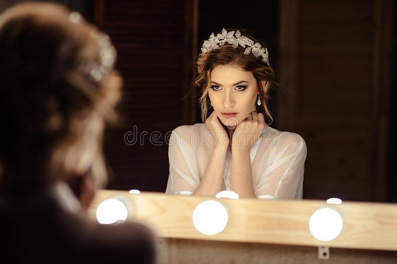 Portrait of blonde bride woman in dressing room with wedding jewelry and dress stock images