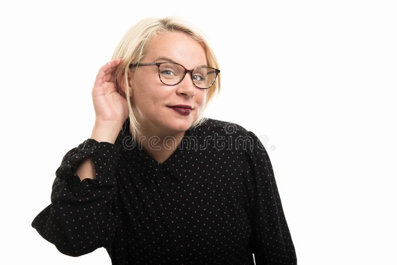 Blonde female teacher wearing glasses showing can`t hear gesture royalty free stock images