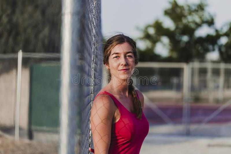 Portrait of young blonde fitness woman runner relaxing on stadium at sunset Sport and healthy lifestyle concept royalty free stock photos