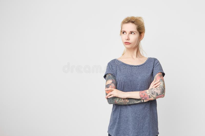 Portrait of young blonde girl with tattoos over her arms wearing casual t-shirt and looking aside. Negative emotions. royalty free stock image