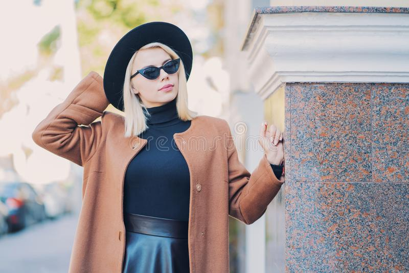 Portrait of young blonde hipster woman in hat in autumn city. Girl have stylish look, sunglasses and nose piercing. Lady royalty free stock photography