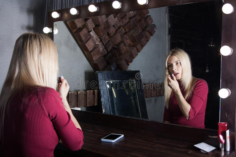 portrait of a young blonde woman in a red dress sitting in front of a makeup mirror and painting her lips with lipstick royalty free stock photography