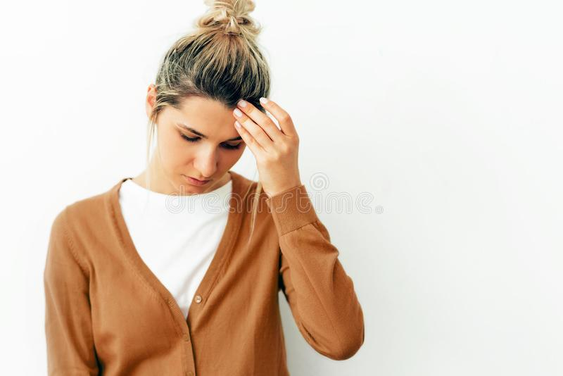 Portrait of young blonde woman having headache migraine. Female student have stress and feels worried. Healthcare and medicine royalty free stock photo
