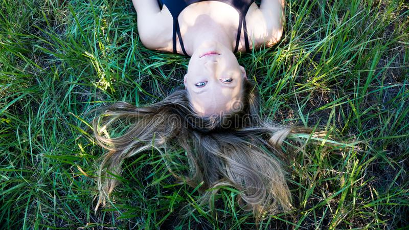 Portrait young blonde woman laying in the grass with long hair and blue eyes stock photos