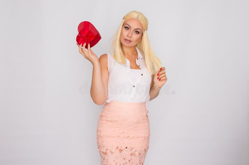 Portrait of a young blonde woman in light-colored clothes. Holding a heart shaped gift box stock photos