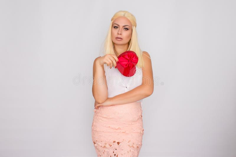 Portrait of a young blonde woman in light-colored clothes. Holding a heart shaped gift box stock photography