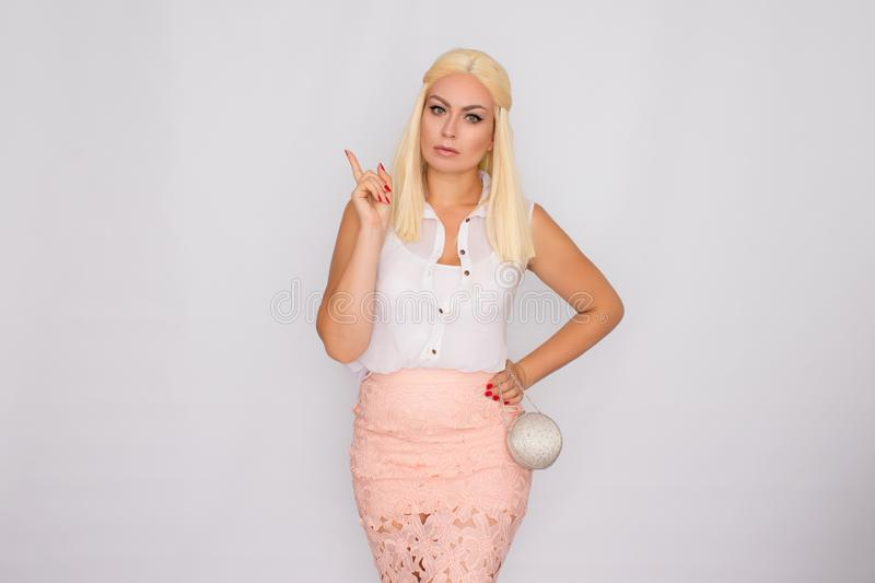 Portrait of a young blonde woman in light-colored clothes holding a small silver handbag in her hands stock photos