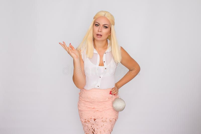 Portrait of a young blonde woman in light-colored clothes holding a small silver handbag in her hands royalty free stock images
