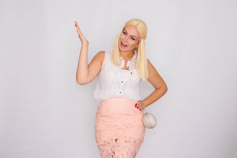 Portrait of a young blonde woman in light-colored clothes holding a small silver handbag in her hands royalty free stock photo