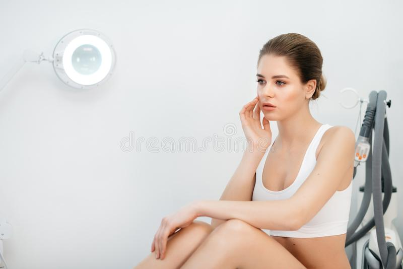 Portrait of young blonde woman in lingerie posing in white salon. Charming woman with natural make-up, porcelain skin royalty free stock image