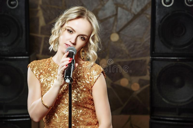 Portrait of young blonde woman with microphone on dark background stock image