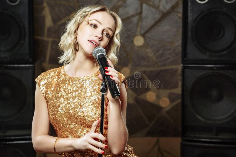 Portrait of young blonde woman with microphone on dark background royalty free stock photography