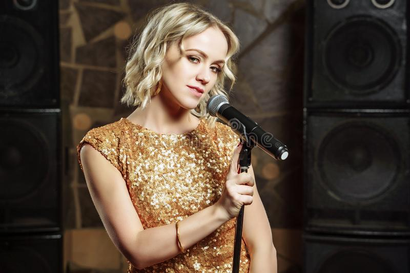 Portrait of young blonde woman with microphone on dark background stock photography