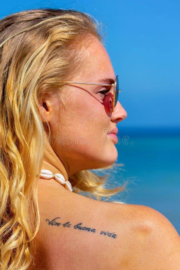 Portrait of young woman with tattoo on shoulder. Portrait of young blonde woman with tattoo `live the good life` in spanish on shoulder royalty free stock photography