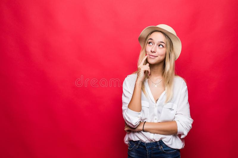 Portrait of young blonde woman wearing in straw hat and touching chin with brooding or dreaming view, isolated over red background stock photo