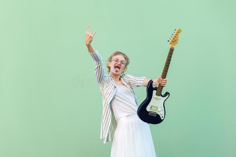 Portrait of young blonde woman in white shirt, skirt, and striped blouse and electric guitar standing with rock sign tongue out stock image