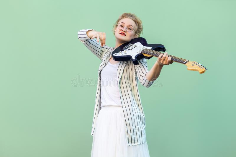 Portrait of young blonde woman in white shirt, skirt, and striped blouse with eyeglasses standing and holding electric guitar and. Looking. indoor studio shot stock photography