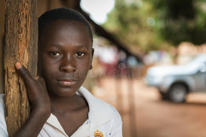 Portrait of a young boy at the entrance of his home in the town of Nhacra in Guinea Bissau. Nhacra, Republic of Guinea-Bissau - January 28, 2018: Portrait of a stock photo