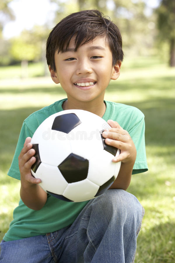 Portrait Of Young Boy In Park With Football stock photo