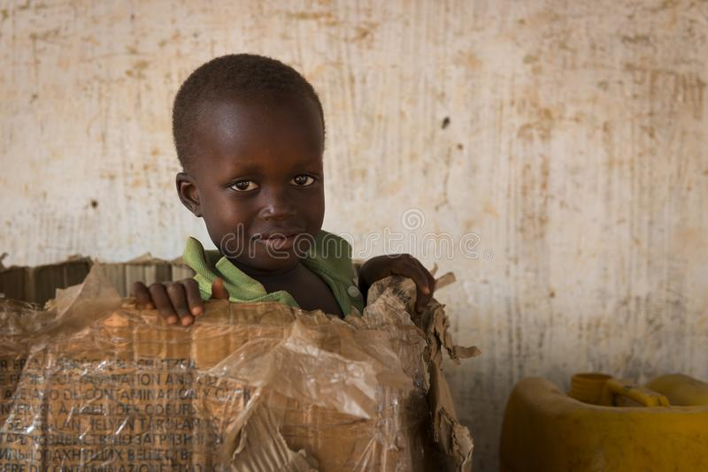 Portrait of a young boy playing in a card box in the town of Nhacra in Guinea Bissau. Nhacra, Republic of Guinea-Bissau - January 28, 2018: Portrait of a young stock image