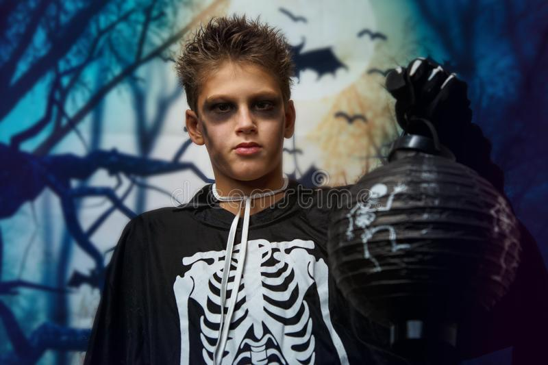 Portrait of young boy in skeleton costume with makeup. Celebration of holiday Halloween, the boy in the image, the skeleton theme. The vampire,bat stock image