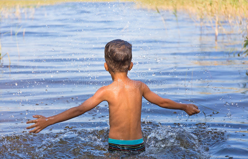 Portrait of young boy swimming and squirting. European baby sprinkles in the lake royalty free stock photos