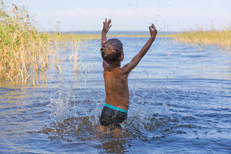 Portrait of young boy swimming and squirting. European baby sprinkles in the lake stock image