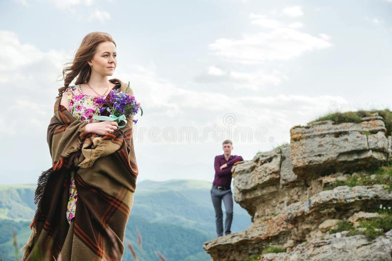 Portrait of a young bride in a colorful dress with a bouquet of wildflowers in the nature standing on the background of stock images