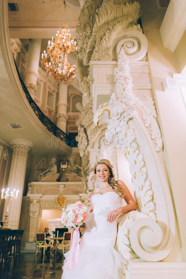 Portrait of a young bride about the white columns stock photo