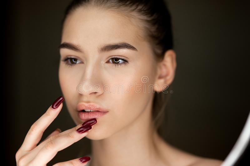 Portrait of young brown-haired girl with natural makeup holding her fingers on her face stock photography
