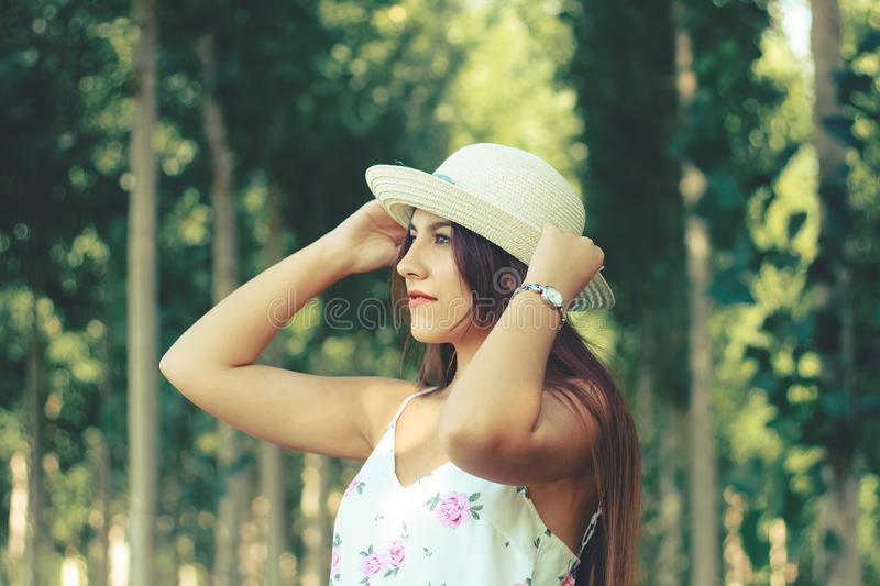 Outdoor portrait of a young beautiful girl  wearing sun white hat and flowery summer dress royalty free stock photos