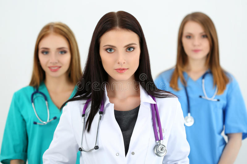 Portrait of young brunette female doctor surrounded by medical team stock photos