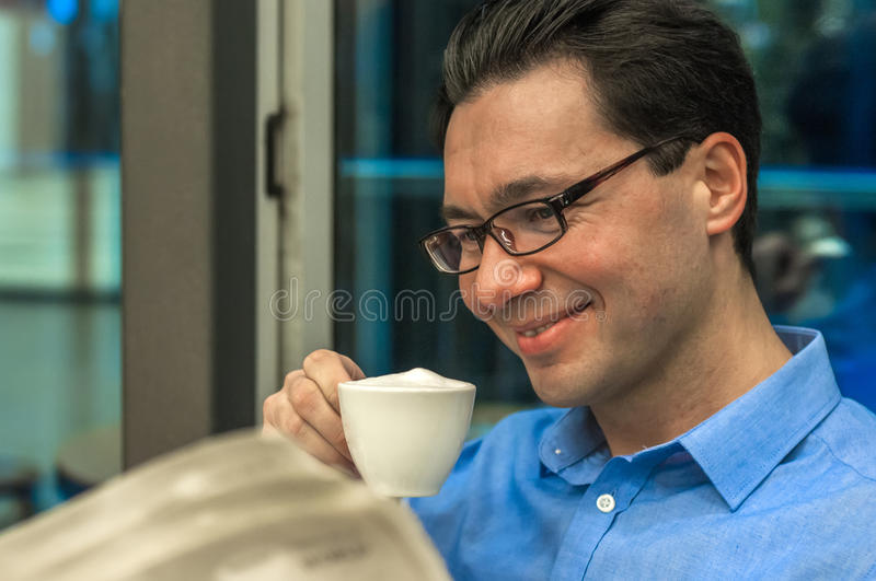 Portrait of young brunette hair businessman sitting in a coffee. Shop reading a newspaper looking concentrated, handsome business man holding open newspaper royalty free stock photography