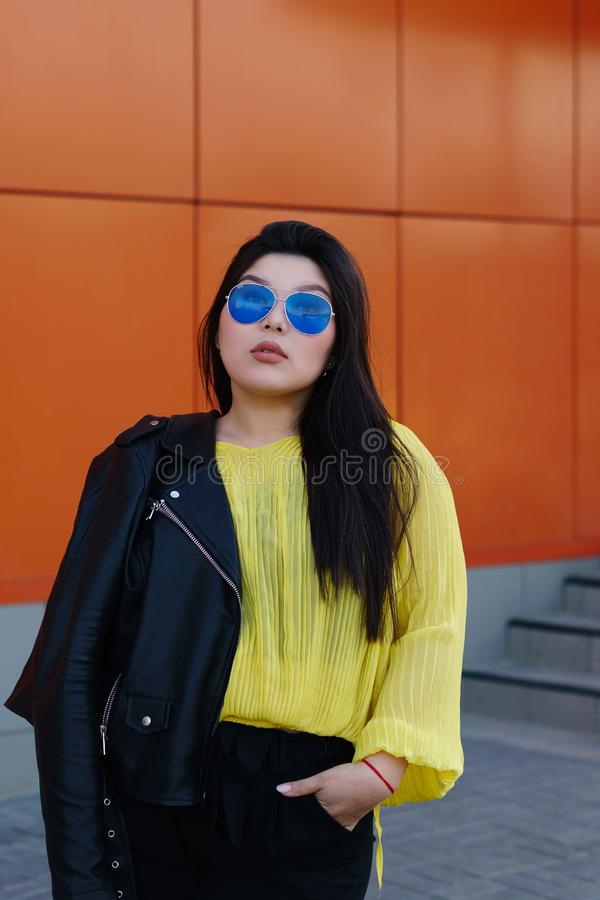 Stylish Pan-Asian girl posing outdoor. Portrait of a young brunette plus size woman. Audacity pan-Asian girl in a biker leather jacket with sunglasses poses near stock photo