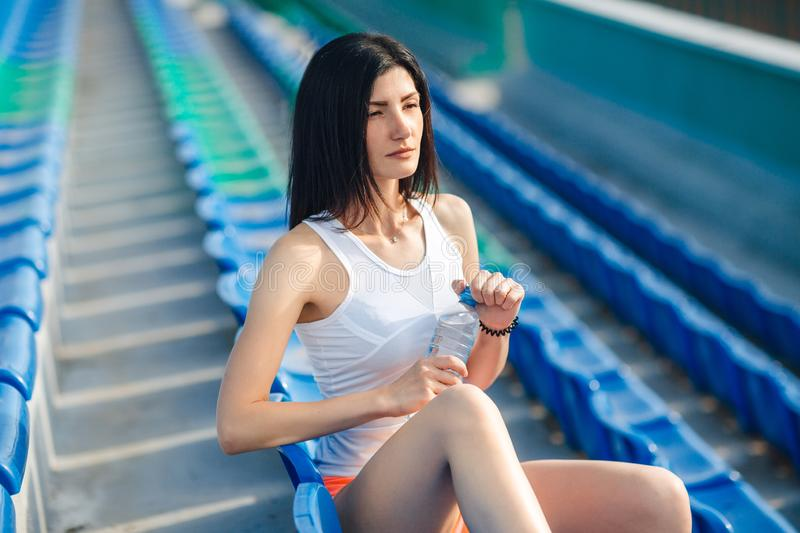 Portrait of Young brunette sport girl with water bottle. Fitness girl in shorts and tank top sitting on the blue seats at the royalty free stock images