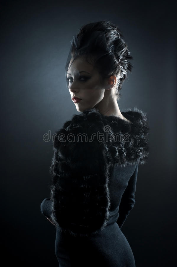 Portrait of a young brunette in a vampire dress. Portrait of a young and attractive brunette Caucasain woman posin in a dark vampire dress. The image is taken on royalty free stock photo