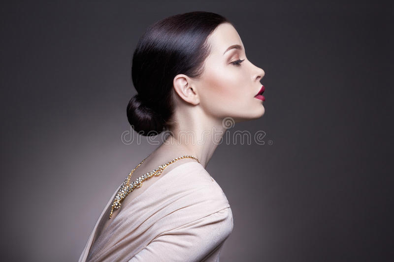 Portrait of young brunette woman against a dark background. Mysterious bright image of a woman with professional makeup. The sensuality and mystery of women royalty free stock photo