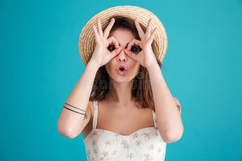 Portrait of a young brunette woman in beach hat. Making sunglasses with her fingers isolated over blue background stock images