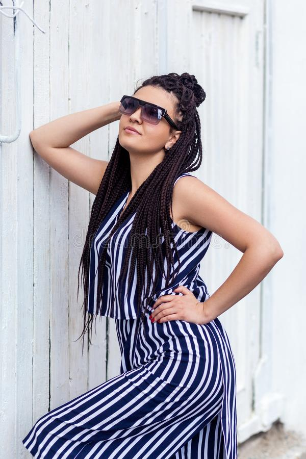 Portrait of young brunette woman with black afro american dreadlocks hairstyle in striped dress and sunglasses, standing, posing royalty free stock photography