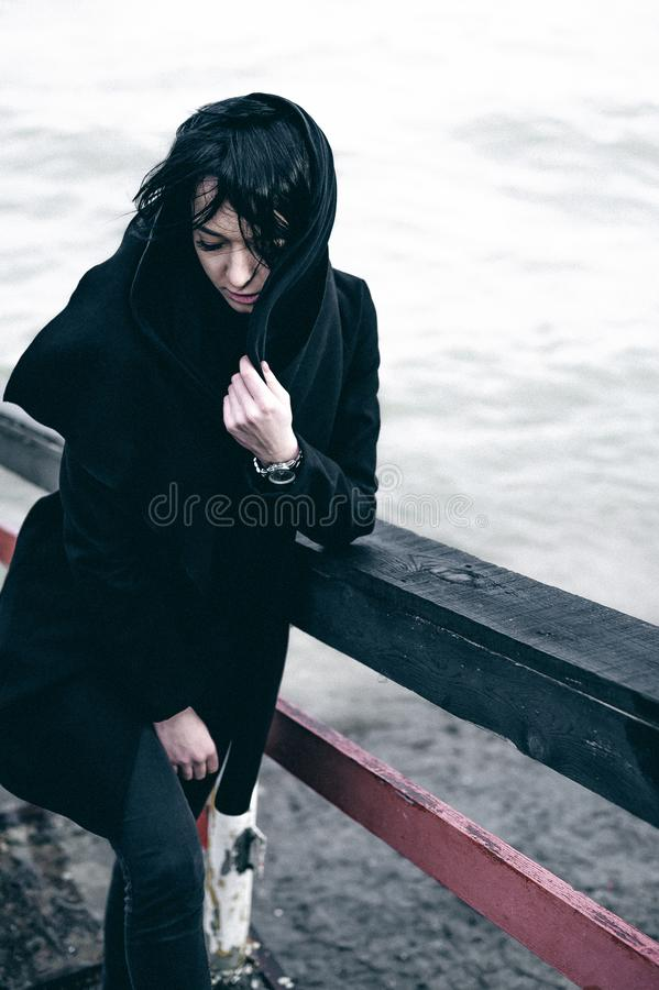 Fashionable portrait of a young brunette woman in black clothes, jeans T-shirt, coat and sunglasses, in a Gothic style sad mood. o. Portrait of a young brunette stock image