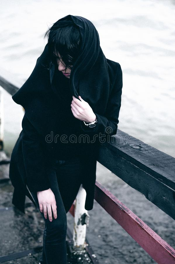 Fashionable portrait of a young brunette woman in black clothes, jeans T-shirt, coat and sunglasses, in a Gothic style sad mood. o. Portrait of a young brunette stock photo
