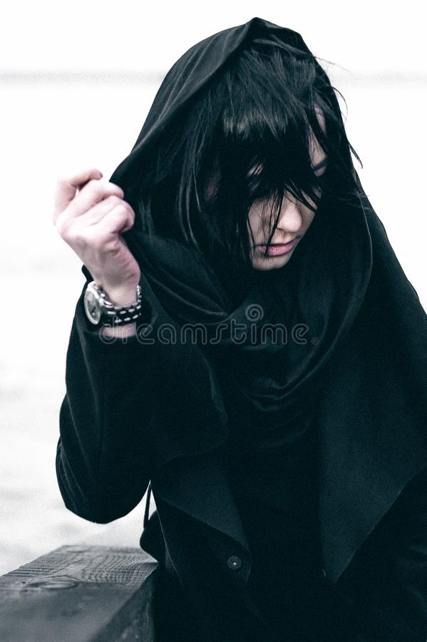 Fashionable portrait of a young brunette woman in black clothes, jeans T-shirt, coat and sunglasses, in a Gothic style sad mood. o. Portrait of a young brunette royalty free stock photos