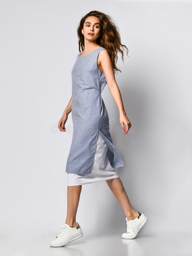 Portrait of a young brunette woman in a blue light dress posing on a light background, Summer fashion, preparing for a date royalty free stock photo