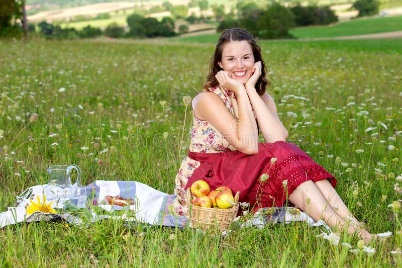 Young brunette woman in dirndl sitting in a field of flowers on a blanket. Portrait of young brunette woman in dirndl sitting in a field of flowers on a blanket royalty free stock photos