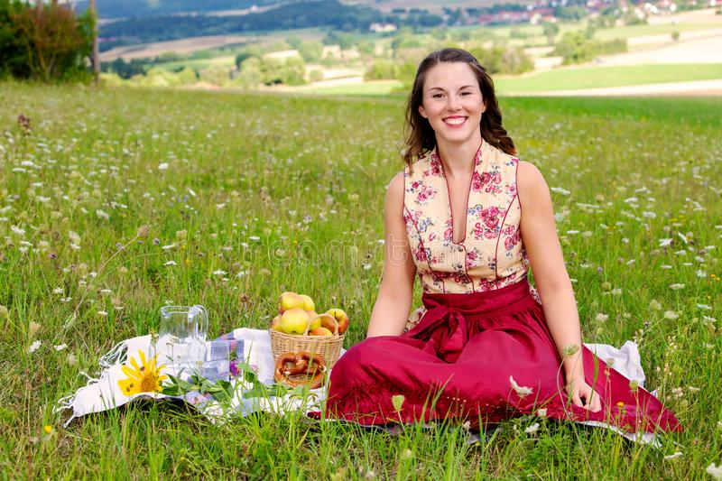 Young brunette woman in dirndl sitting in a field of flowers on a blanket. Portrait of young brunette woman in dirndl sitting in a field of flowers on a blanket stock photo