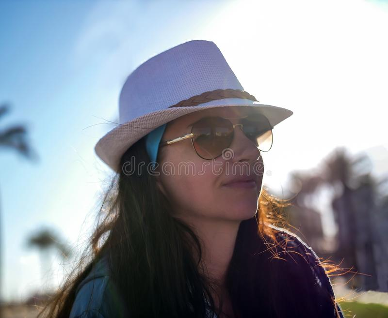 Portrait of a young woman in glasses and a hat in the sun royalty free stock images