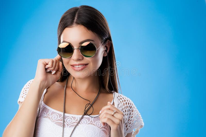 Portrait of young brunette woman hiding her ear by finger, listening music in headphones. Wearing white top, knit. Cardigan and sunglasses.Studio isolate on stock image
